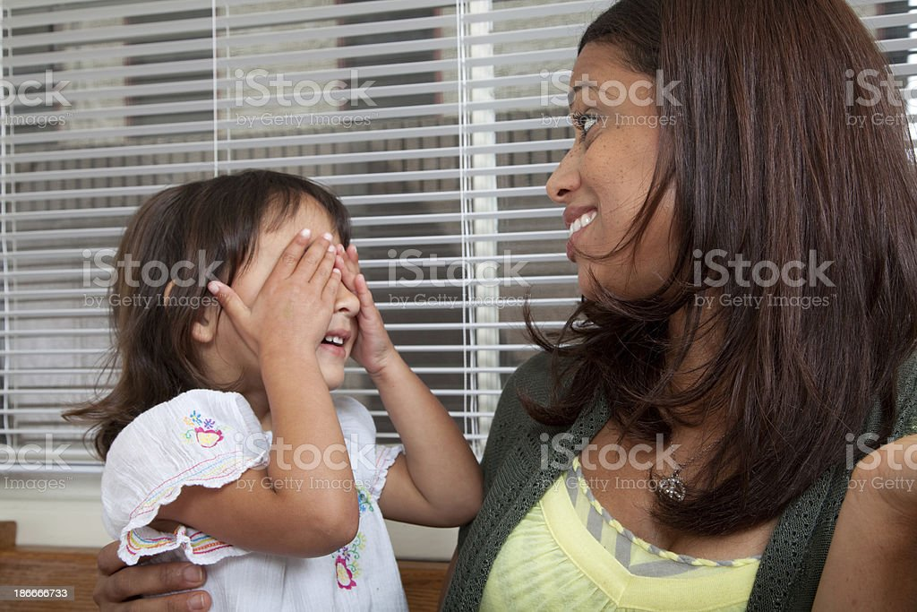 Mother and daughter playing peek a boo royalty-free stock photo