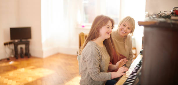mother and daughter playing piano playing the piano at home persons with disabilities stock pictures, royalty-free photos & images