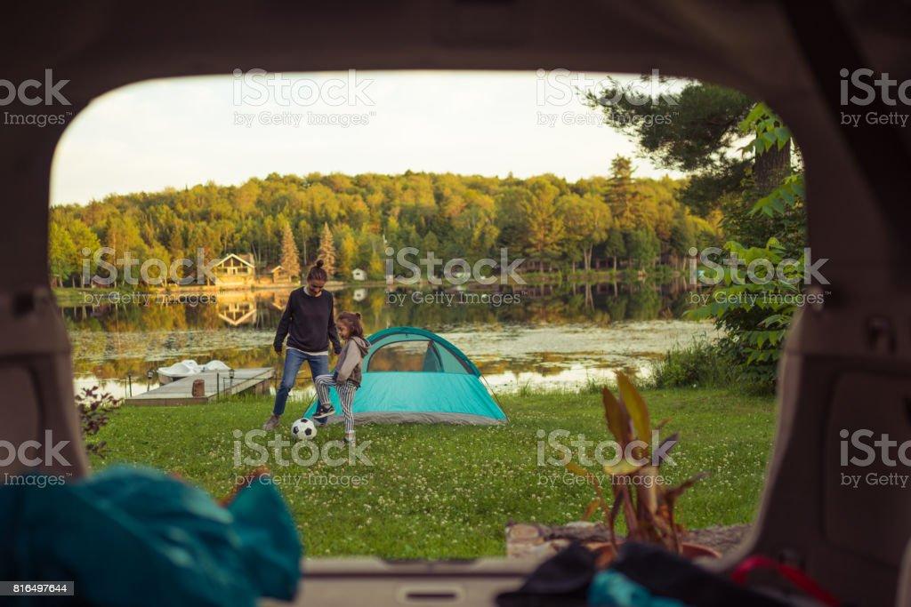 Madre e hija jugando al fútbol por el lago - foto de stock