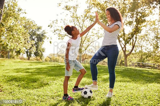 istock Mother And Daughter Playing Soccer In Park Together 1030913172