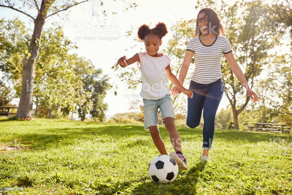 Moeder en dochter te voetballen In het Park samen foto