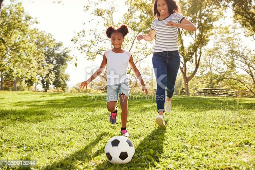 829627936istockphoto Mother And Daughter Playing Soccer In Park Together 1030913244