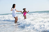 African American mother (30s) and daughter (6 years) at the beach, playing in the surf.