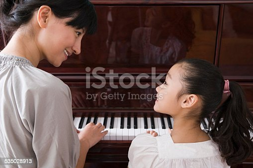 511527698 istock photo Mother and daughter playing the piano 535028913