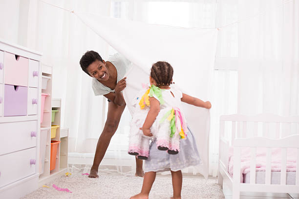 mother and daughter playing time at home. - pferde schlafzimmer stock-fotos und bilder