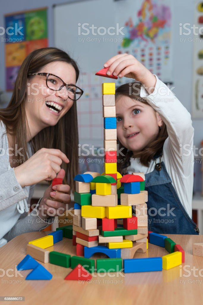 Mother and Daughter Playing Together with colorful building toy blocks stock photo