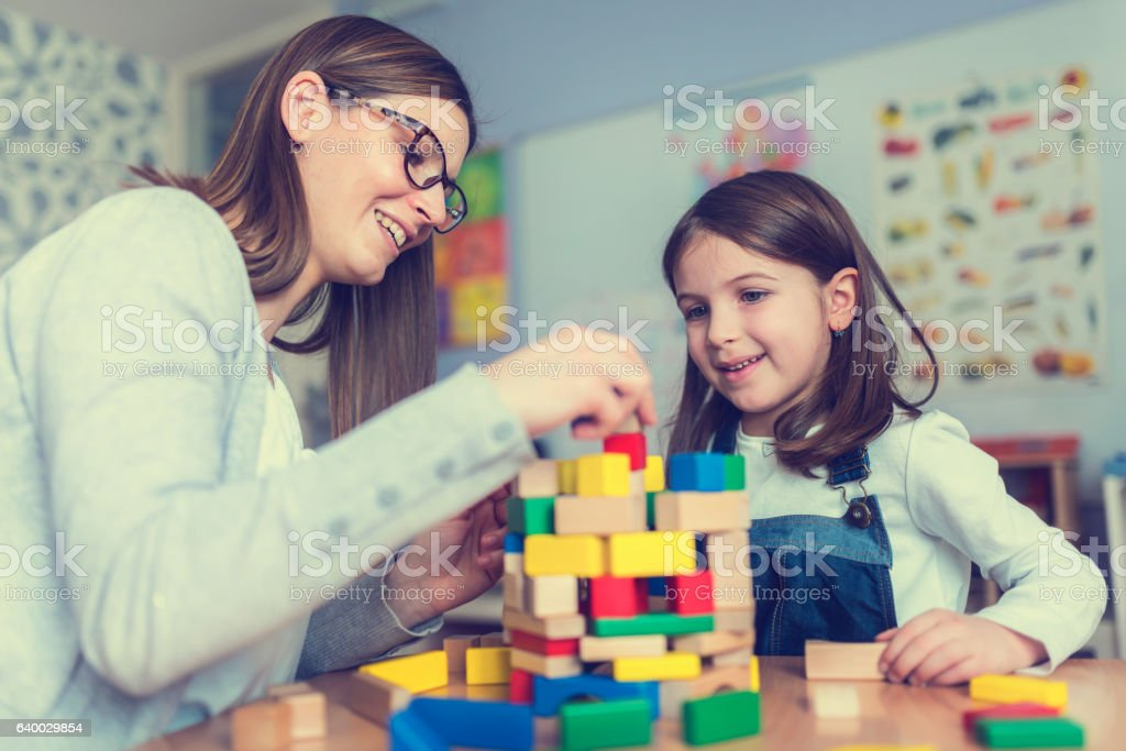 Mother and Daughter Playing Together with colorful building toy blocks - foto de stock