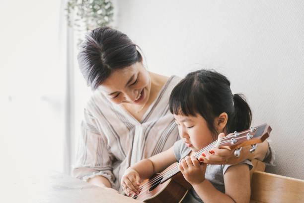 Mãe e filha jogando ukulele em casa - foto de acervo