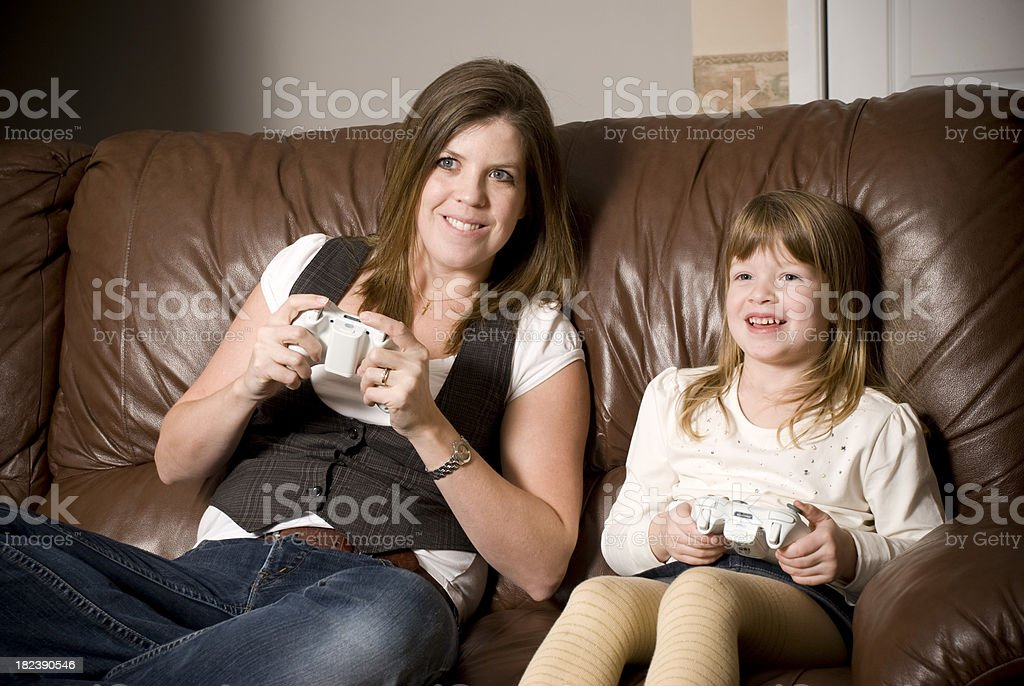 Mother and daughter playing video game console royalty-free stock photo