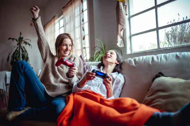 Mother and daughter playing video games Mother and daughter playing video games. Mommy is winning leisure games stock pictures, royalty-free photos & images