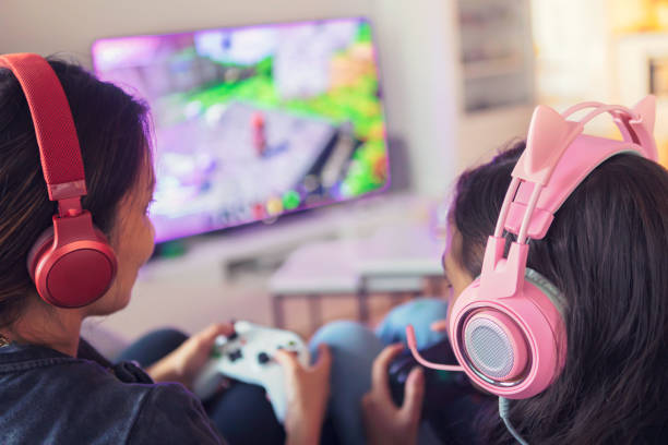 Mother and daughter playing video games together stock photo
