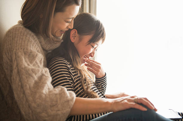 mother and daughter playing with a digital tablet in bedroom - 母娘 笑顔 日本人 ストックフォトと画像