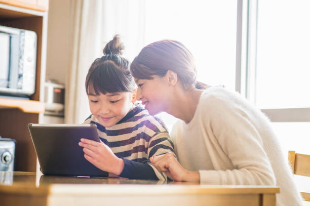 mother and daughter playing with a digital tablet in room - game of life stock photos and pictures