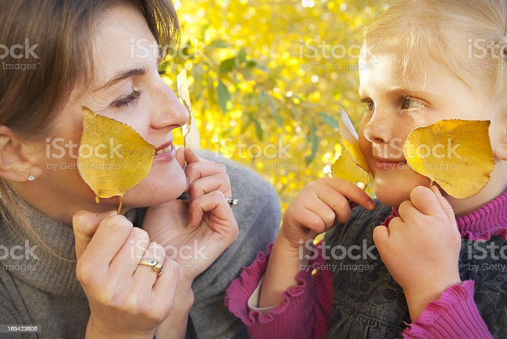 Mother and daughter, playing with autumn yellow leaves royalty-free stock photo