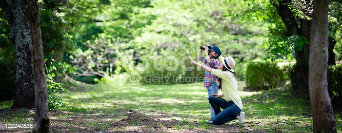 Mother and daughter playing with binoculars in the woods