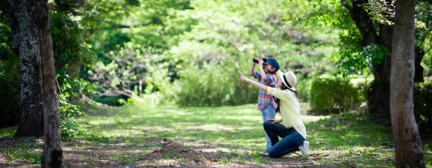 Mother and daughter playing with binoculars in the woods stock photo