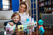 Beautiful young mother and cute baby daughter playing with construction toys in their living room.