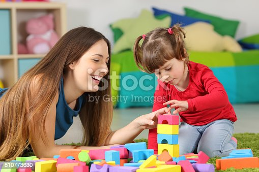 istock Mother and daughter playing with construction toys 810773630