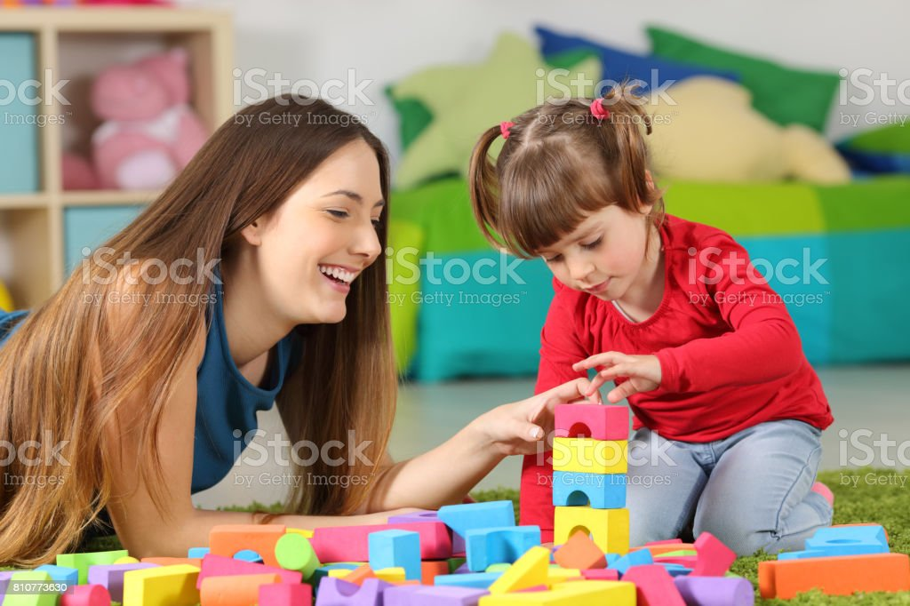 Mother and daughter playing with construction toys stock photo