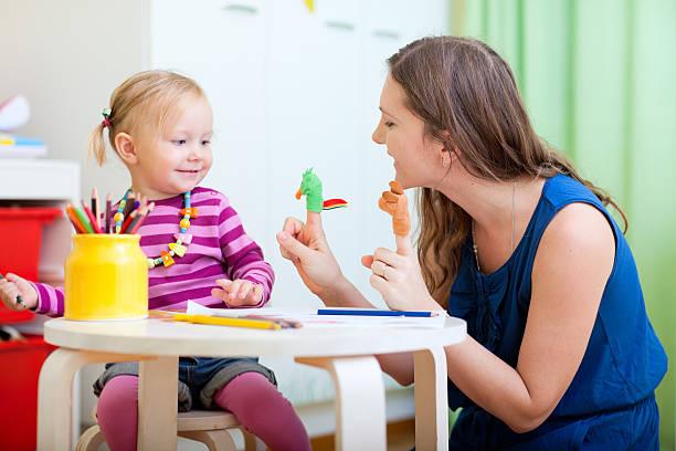 Madre e hija jugando con juguetes de dedos - foto de stock