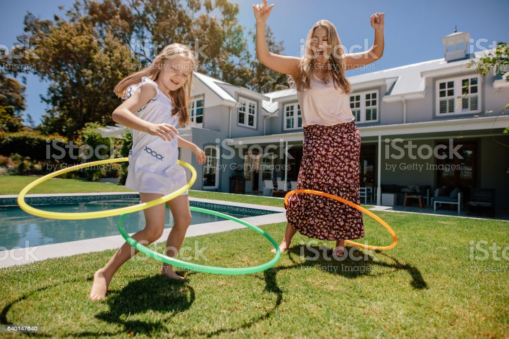 Mother and daughter playing with hula hoop in their backyard stock photo