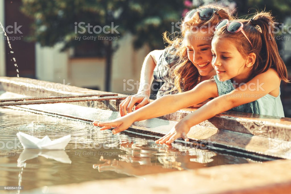 Mother and daughter playing with paper boats in the fountain in they garden. stock photo