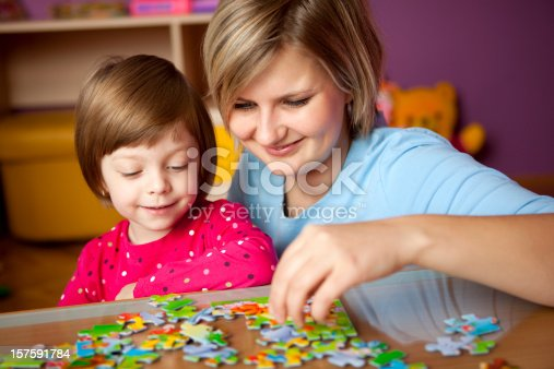 istock Mother and daughter playing with puzzle 157591784