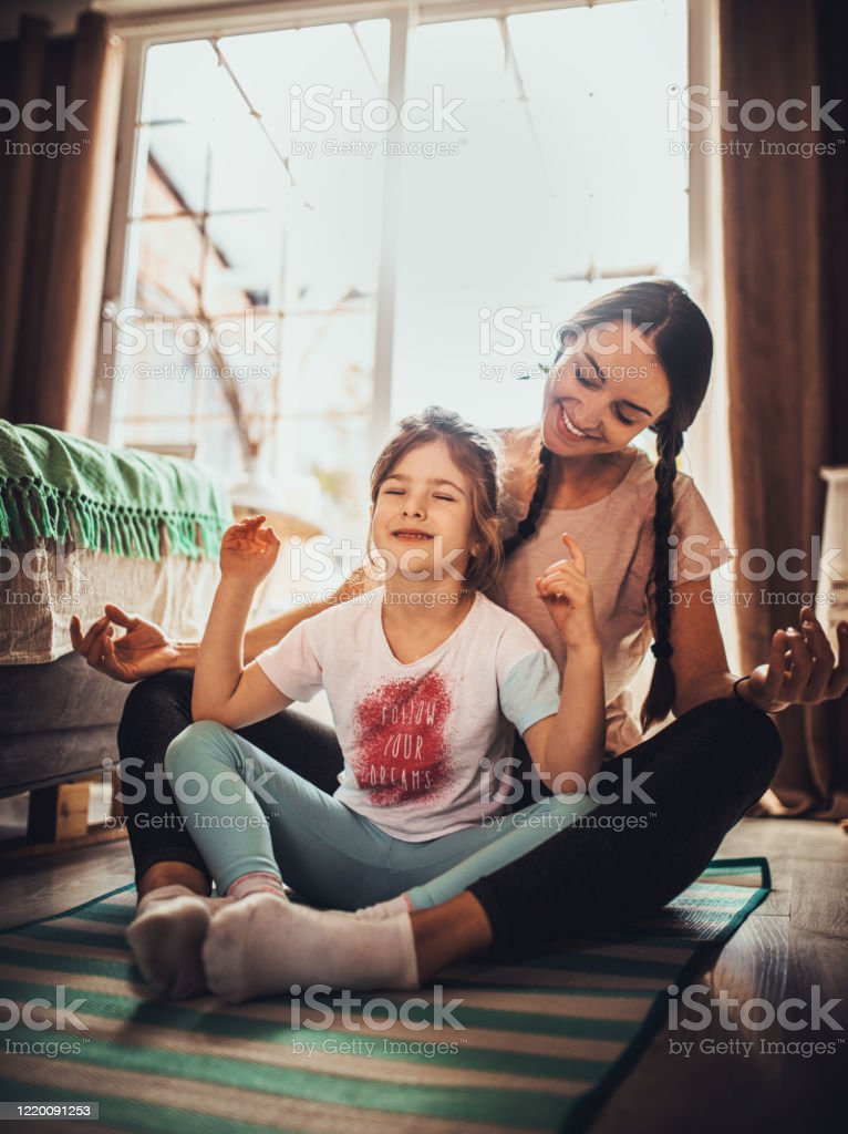 Mother and daughter practicing  in bedroom Mother and daughter practicing  in bedroom and meditating 30-34 Years Stock Photo