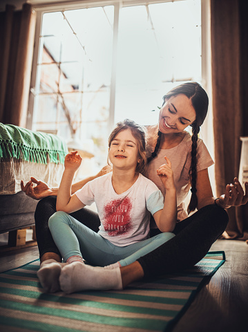 Mother And Daughter Practicing In Bedroom Stock Photo - Download Image Now