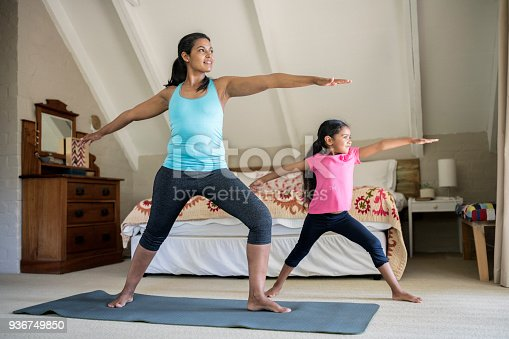 Mother and daughter practicing yoga. Females are exercising in bedroom. They are at home.