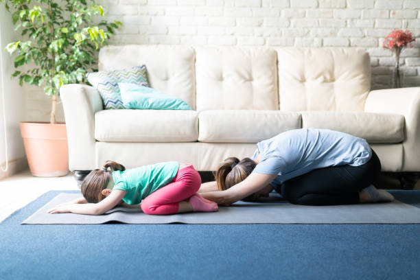Mother and daughter practicing yoga Both mother and daughter exercising together and doing yoga child's pose in the living room at home childs pose stock pictures, royalty-free photos & images
