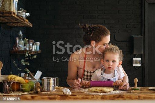 istock Mother and daughter prepare cookies in kitchen 971858418