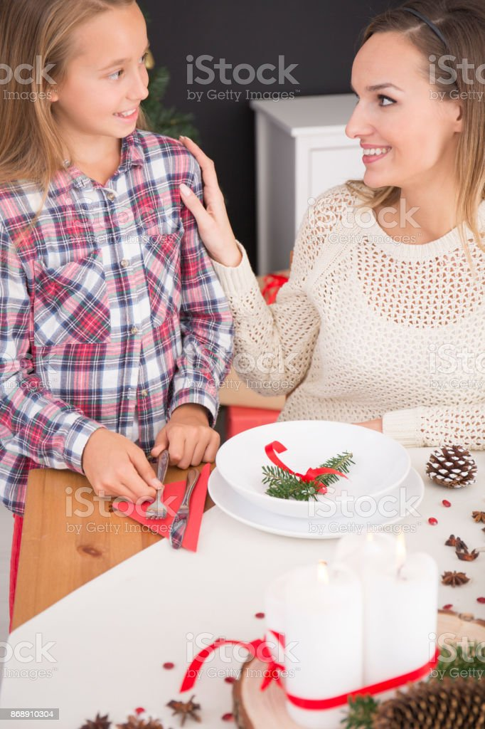 Mother and daughter preparing Christmas table stock photo