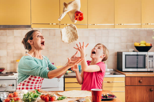 Mother and daughter preparing pizza stock photo