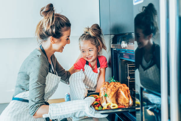 mother and daughter preparing turkey - christmas cooking foto e immagini stock