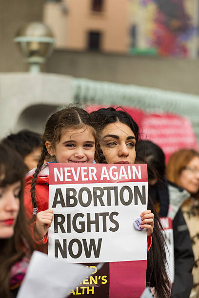 Mother and daughter protesting Dublin, Ireland - March 8, 2014: Mother and daughter supports abortion rights in Ireland during International Women's Day Protest Dublin organised by ROSA organisation pro choice stock pictures, royalty-free photos & images