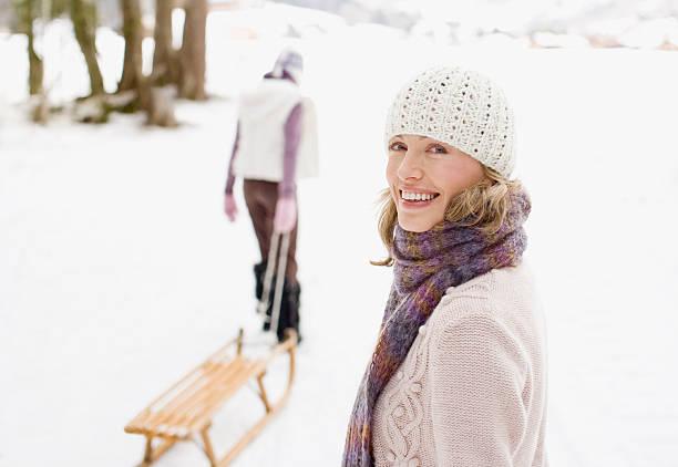 mutter und tochter ziehen schlitten durch den schnee - mützenschal stock-fotos und bilder