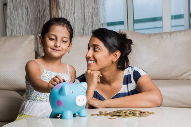 Mother and daughter putting coins into piggy bank - Stock image Family, Offspring, One Parent, Daughter, Single Mother indian family stock pictures, royalty-free photos & images