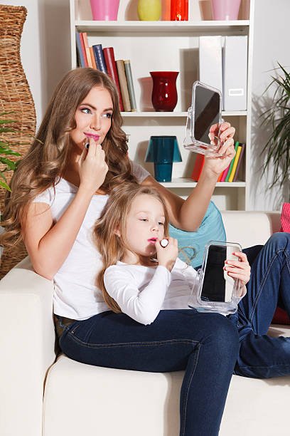 mother and daughter putting lipstick on - makeup for pregnant women stock photos and pictures