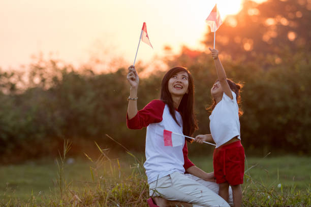 mãe e filha, levantando a bandeira da indonésia - bandeira da indonesia - fotografias e filmes do acervo