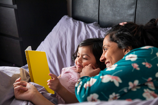 A mid adult woman and her daughter lying down in bed and reading a book together. It is the morning and they are both wearing pyjamas.