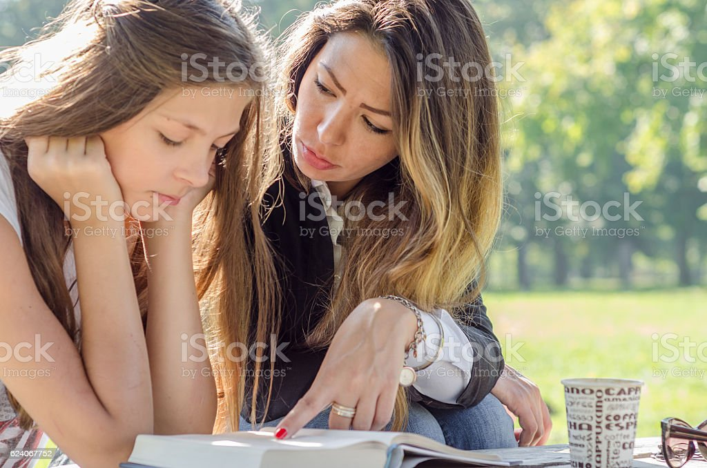 Mãe e filha lendo um livro - foto de acervo