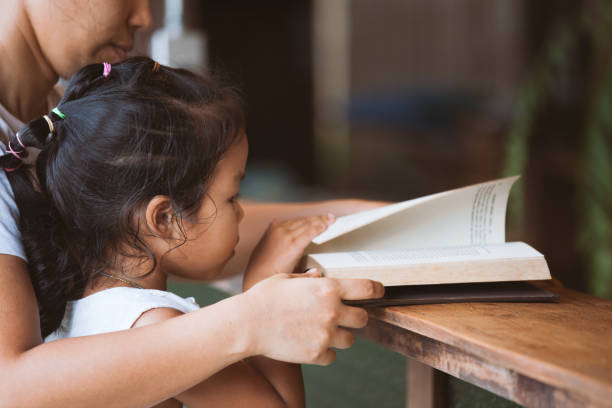 Mother and daughter reading a book together in the house stock photo