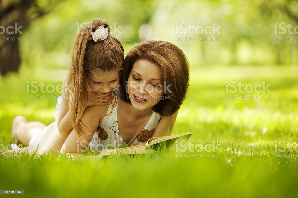 Mother and daughter reading book in park royalty-free stock photo
