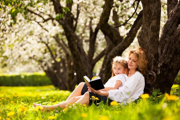 Mutter und Tochter lesen Buch im park – Foto
