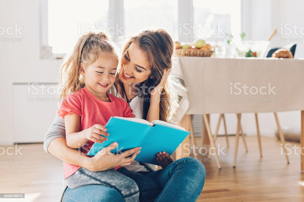 Mother and daughter reading book stock photo