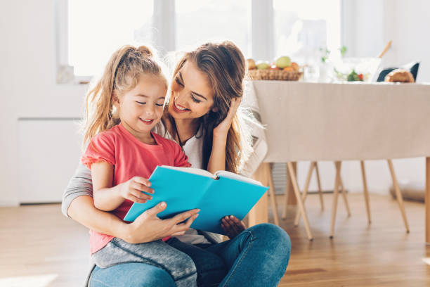 mother and daughter reading book - a little girl reading a book stockfoto's en -beelden
