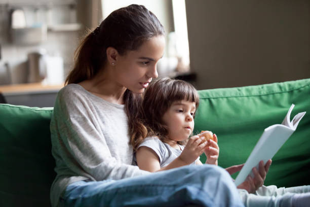Mother and daughter reading book sitting on sofa at home stock photo