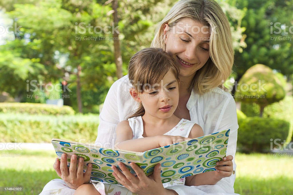 Mother and daughter reading in the park royalty-free stock photo