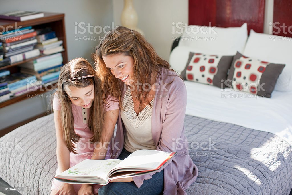 Mother and daughter reading on bed stock photo
